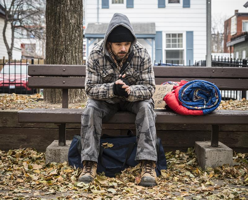 Homeless Veteran sits on a park bench with his sleeping bag.