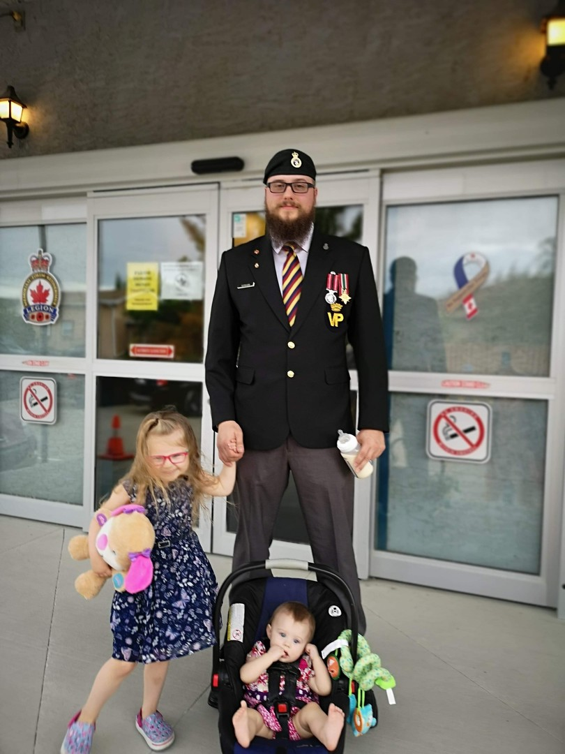 Veteran and Legion member Brandon stands for a photo outside the Legion with his two young children.