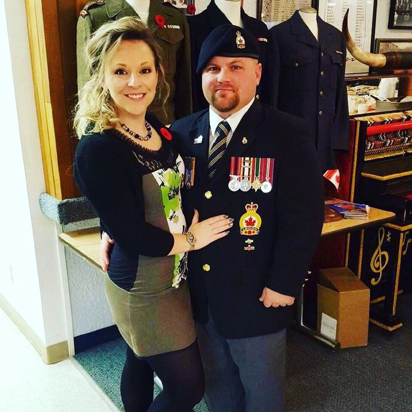 A young Veteran Legion member dressed in his Legion uniform poses for the camera with his wife. They are indoors at a Royal Canadian Legion branch.