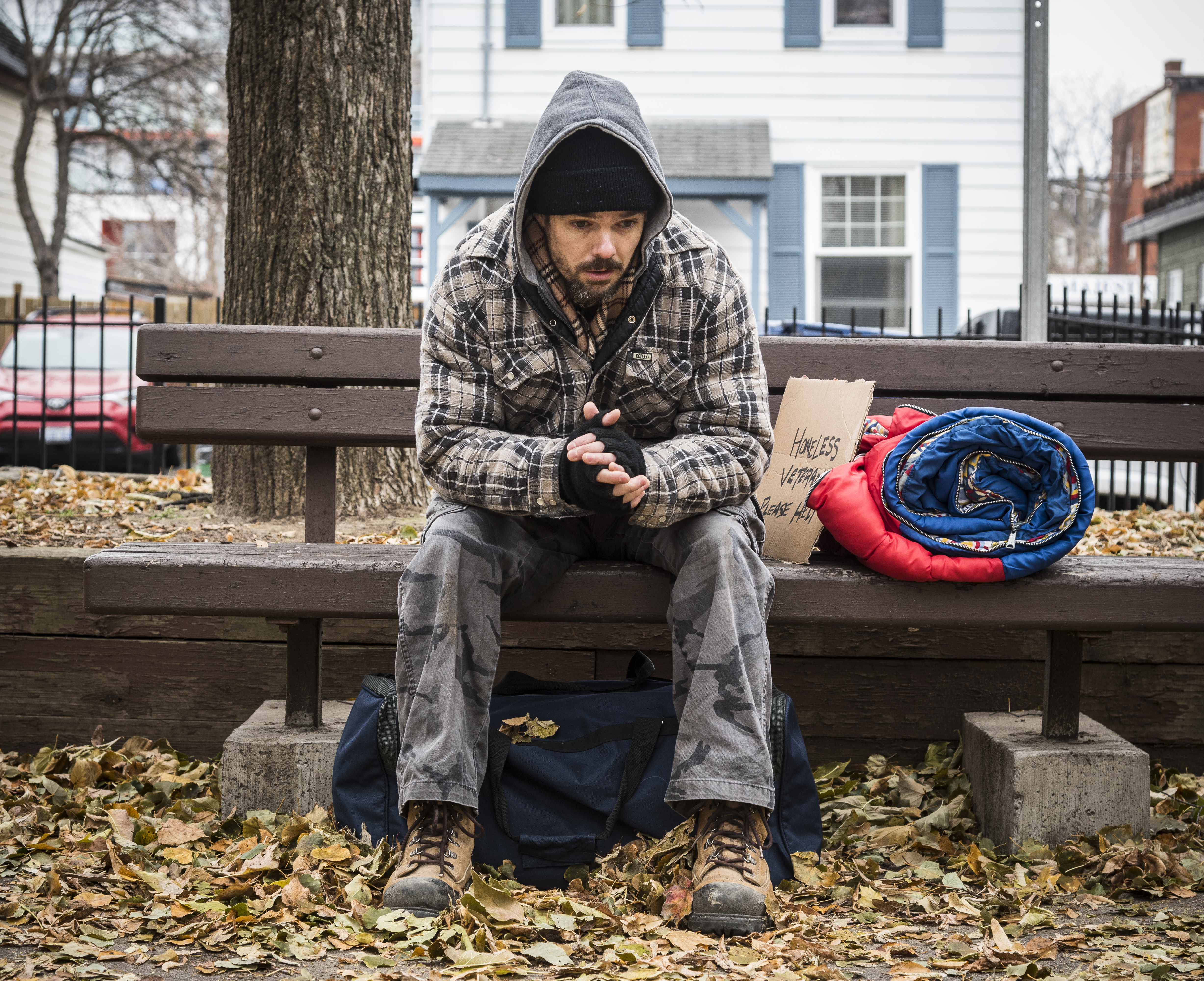 Homeless veteran sits on a bench in a park.