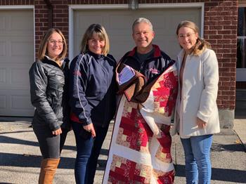 Recipient of a Quilt of Valour, CPO1(Ret'd) Sylvain Bolduc, accompanied by daughter Bianca (far left), wife Denise (his left) and daughter Jessika (his right).